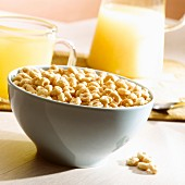 A cup full of ring-shaped cereal and glasses of orange juice