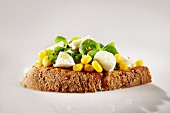 An open sandwich on farmhouse bread with lamb's lettuce, sweetcorn and pink pepper
