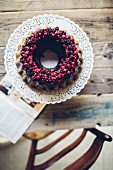 A ring-shaped Bundt cake with berries and chocolate glazing