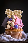 A cupcake decorated with biscuits and sweets