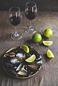 Cooked mussels served with lime wedges and red wine