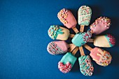 Different cake pops in the shape of ice lollies with brightly coloured icing