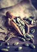 An arrangement of pumpkin seeds on a wooden scoop