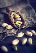 An arrangement of pistachios on a wooden scoop