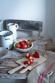 Strawberries in a small bowl and on a chopping board on a rustic wooden table