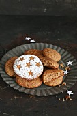 Gluten-free homemade gingerbread decorated with stars and icing sugar on a tin plate