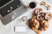 Frühstück im Büro mit Tasse Kaffee und süssen Brezeln