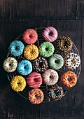 Colorful mini American donuts on wooden background