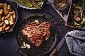 A grilled, dry-aged T-bone steak with roasted potatoes and vegetables
