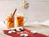 Apple punch with cinnamon and cream in glasses, with vanilla horn biscuits