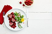 Venison fillets with cherry sauce and a herb salad