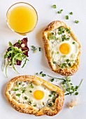 Mini pizzas with fried eggs and a glass of orange juice