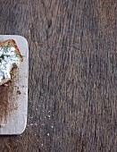 A slice of bread with herb quark on a rustic wooden background