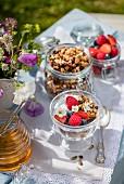 Honig-Granola mit Joghurt und Beeren auf Tisch im Freien