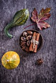 An Autumnal still life with pumpkins, spices and a laurel leaf (top view)