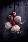 Three beetroots on a black wooden background (seen from above)