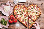 A hand taking a slice from a heart shaped pizza