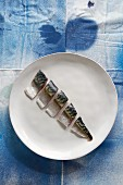 A raw mackerel cut into pieces on a plate (top view)