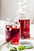 Hibiscus iced tea in a screw top glass jar and a decorative glass bottle
