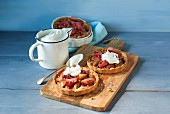 Rhubarb tartlets with whipped cream on a wooden board