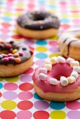 Colourful decorated donuts on a dotted tablecloth