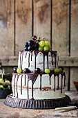 A two tier buttercream cake with grapes and a chocolate glaze
