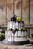 Zweistöckige Buttercremetorte mit Schokoladenglasur und Weintrauben