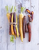 Colourful carrots on a white wooden background