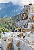 Excavators and diggers getting blocks of marble from the stone quarry in the Apuan Alps, Carrara, Italy
