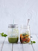 A green smoothie and a vegetable salad in glass jars (half full)