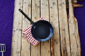 A frying pan and a checkered cloth on a wooden background