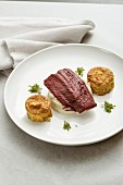 A fillet of beef poached in beetroot sauce with white celery puree, and amaranth and sweet potato cakes