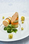 Lime, basil, and apple balls with small salmon rolls on wild herbs