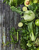 Various green fruits and vegetables on a wooden background
