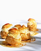 Profiteroles filled with cream and drizzled with caramel