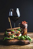 Homemade caprese sandwich, glass of red wine and dried tomatoes in jar on wooden board, dark background