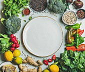 Clean eating healthy cooking ingredients: Vegetables, beans, grains, greens, fruit, spices over grey marble background, white plate with copy space in center