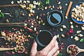 Chinese black tea in black stoneware cups, man's hand holding one cup and wooden spoons with dry herbs