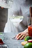 A woman is pouring ice into a margarita glass to make margaritas
