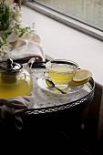 Zitronen-Ingwertee mit Honig in Glaskanne und Tasse auf Tablett am Fenster