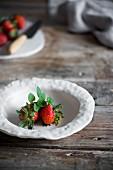 Erdbeeren in Schüssel auf rustikalem Holztisch in Landhausküche