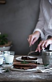 A woman cutting a chocolate pancake on a rustic wooden table
