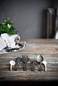 Vintage cutlery in a row on a rustic wooden table