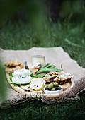 Picknick auf Holztablett und Leinentuch im Garten
