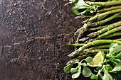 Grüner Spargel, Feldsalat und Zitronenscheiben auf Vintage-Untergrund