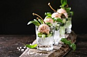 Verrines appetizer with salmon pate, red caviar, cucumber, cream cheese, herbs, capers in glasses served with pink salt and basil