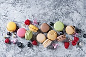 Variety of colorful french sweet dessert macarons with different fillings served over gray texture background