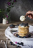 A stack of ricotta pancakes with berries and cream on a rustic wooden table