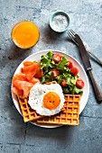 Waffles with smoked salmon, egg, salad and a glass of orange juice