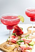 Watermelon margarita in margarita glasses standing on a wooden board